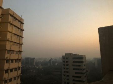 view of buildings and sunrise from a tall building window