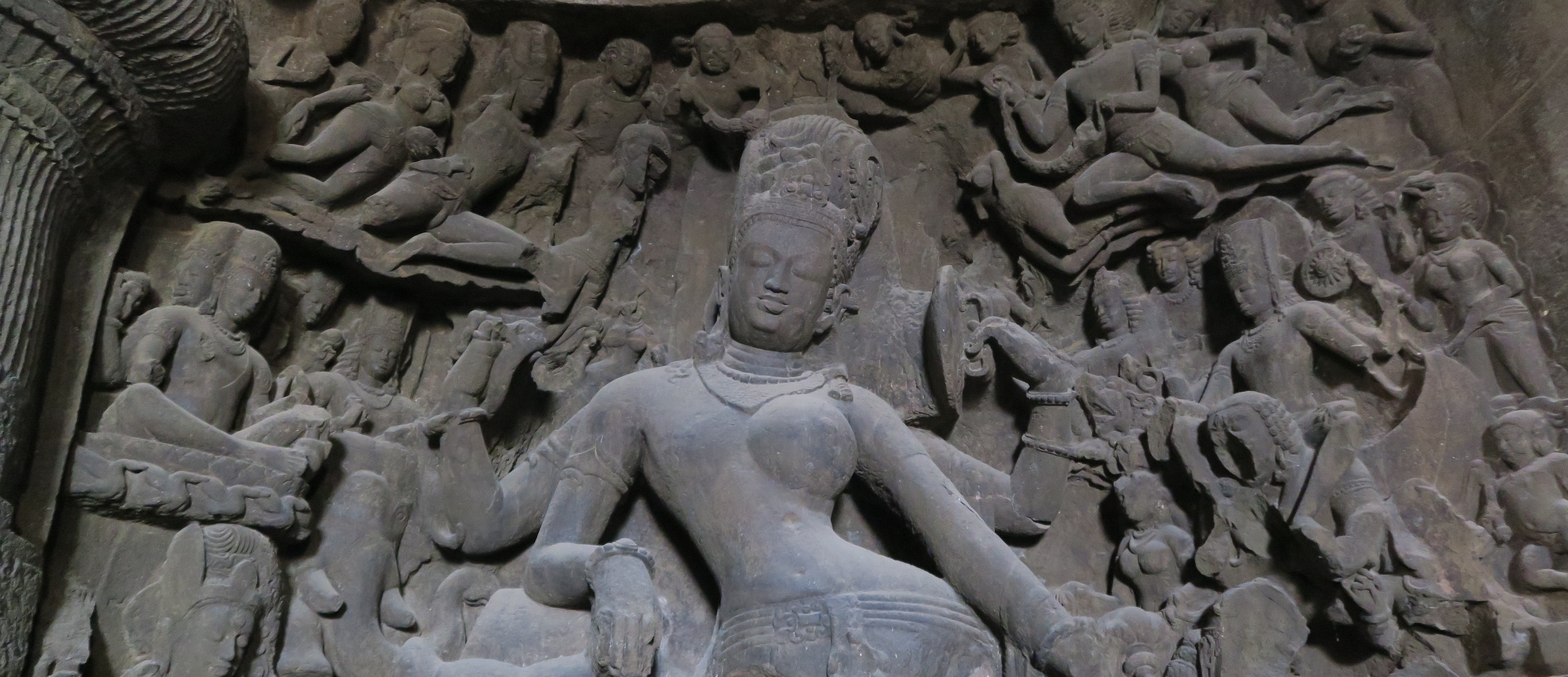 Bas relief of a female deity surrounded by many smaller carvings