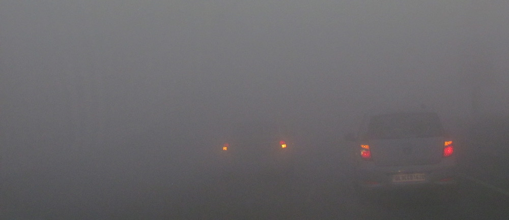 Rear lights of vehicles barely visible in fog