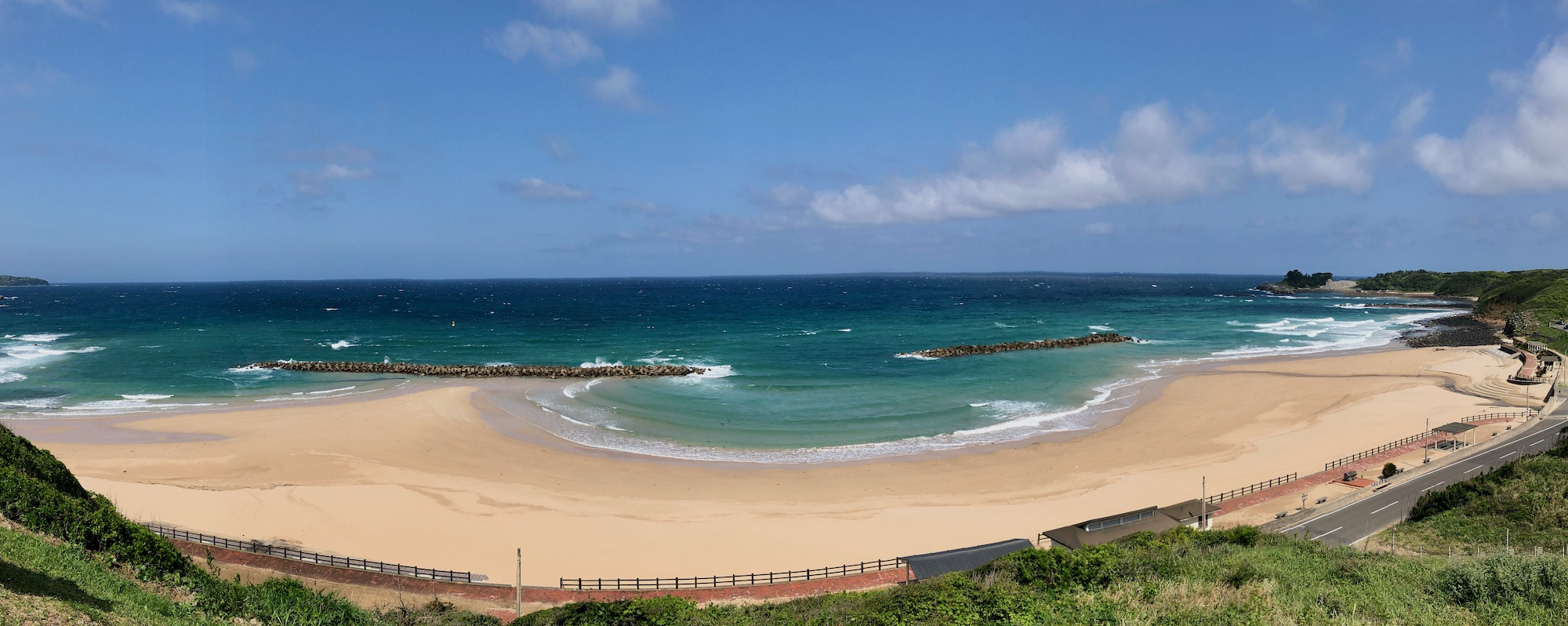 Panorama of wide sandy beach, blue sky, and blue-green waves crashing on the beach