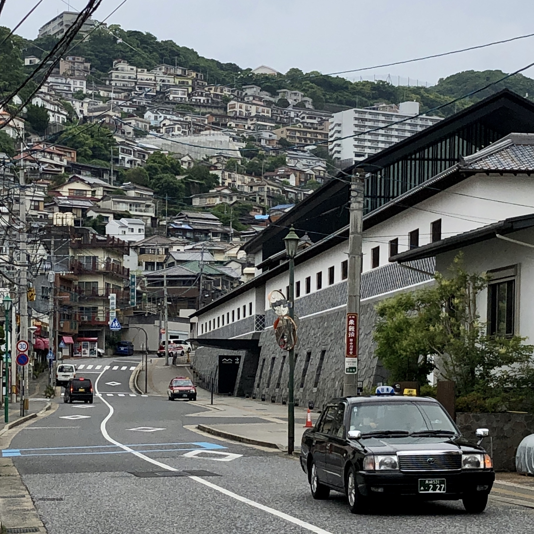 Street in front of a building, with hill behind and many houses and buildings on a steep hill