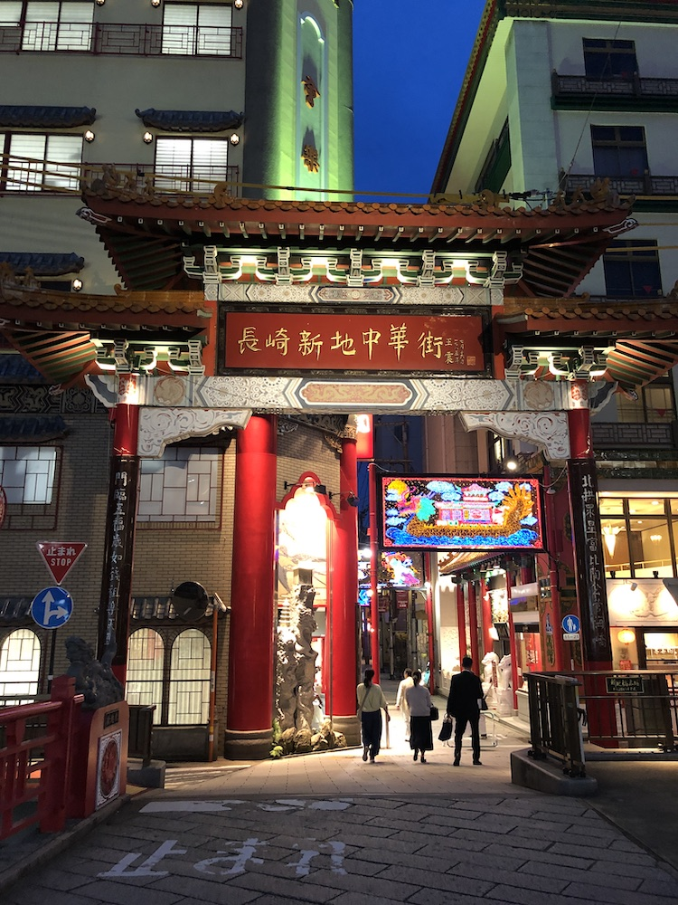 "People walk through a Chinese fluted gate and under neon lights. There is a  sign with Chinese text for ""Nagasaki Shinchi Chinatown"""