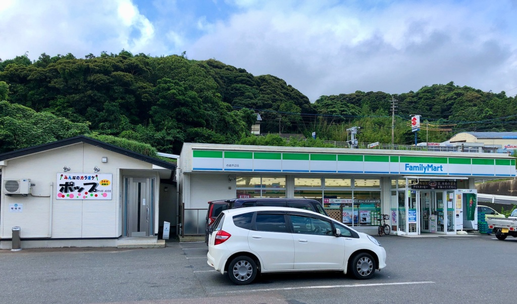 "On the right is a convenience store. Beside it to the left is a small building with a sign for ""Pop"""