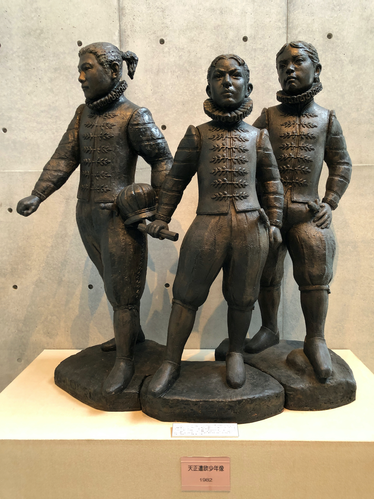 statues of 3 boys in 16th C European clothes