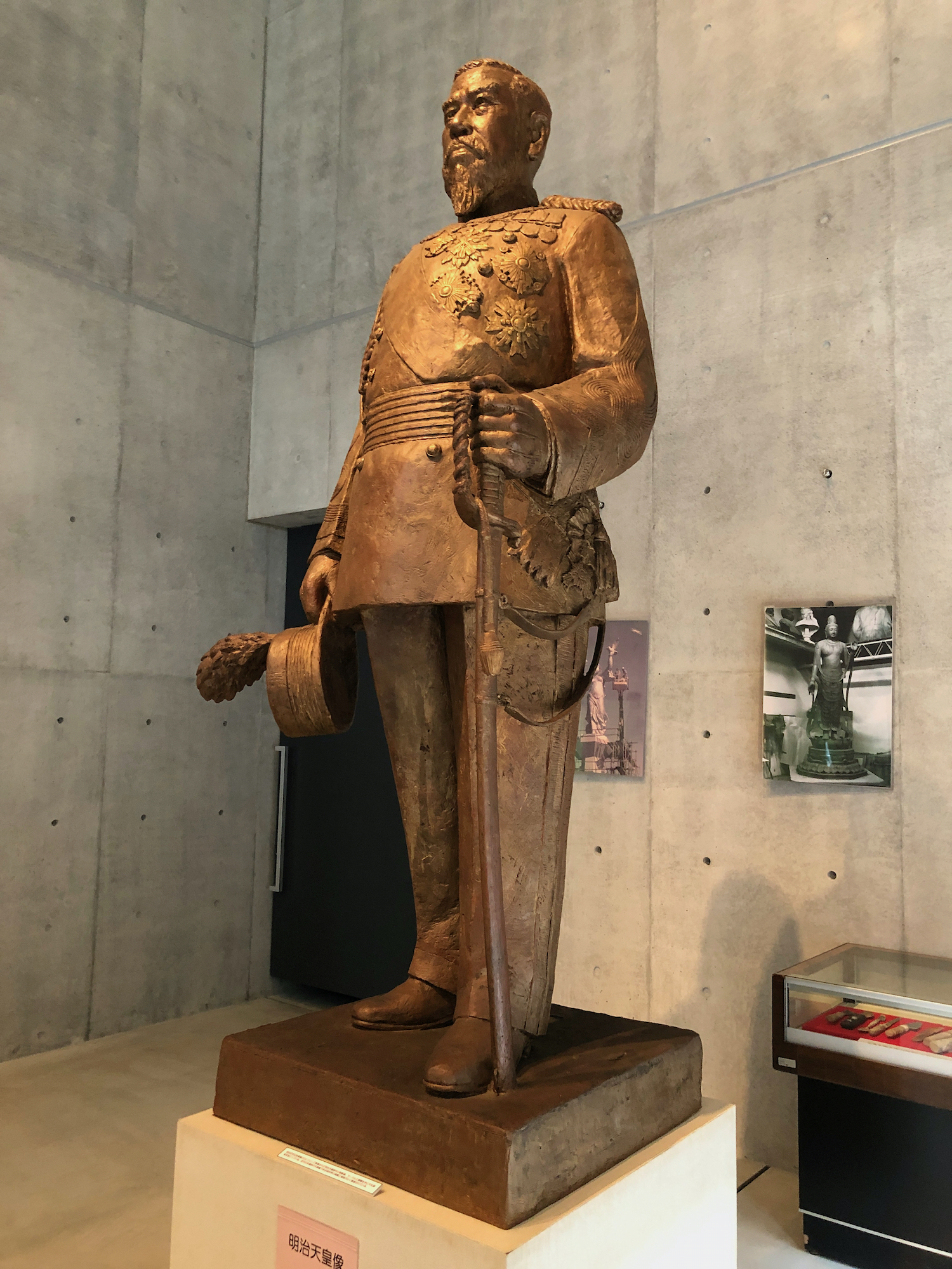 Statue of Meiji emperor in military regalia holding a sword and hat with plume (full size)