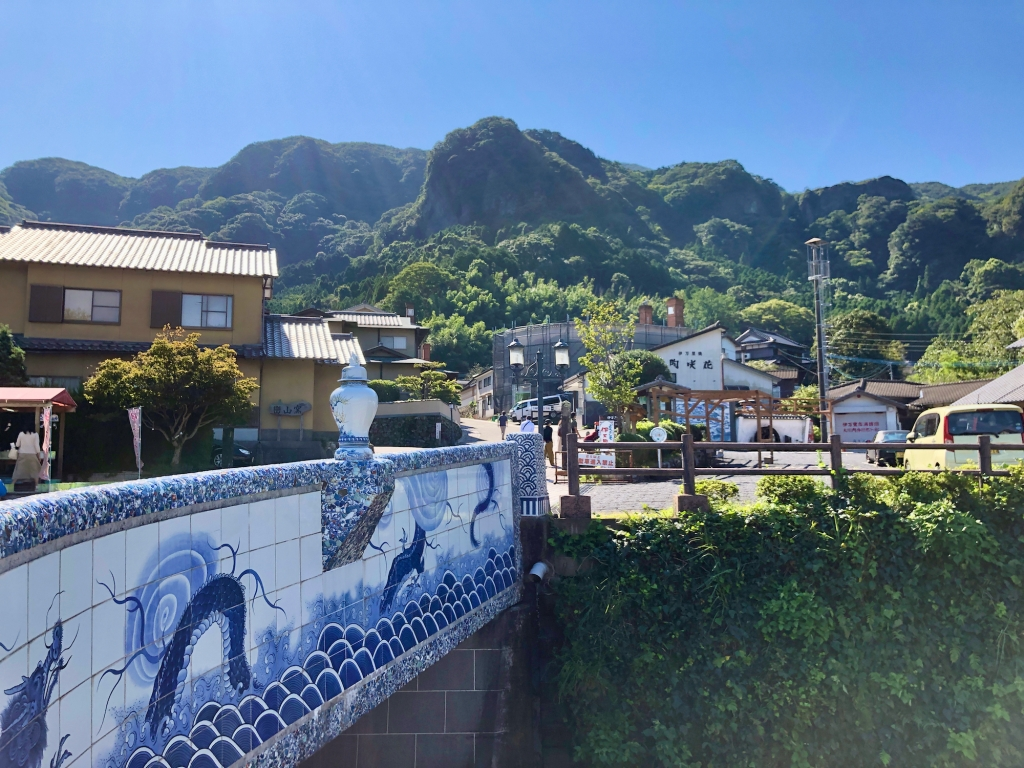 Bridge decorated with ceramic tiles crosses a river to a small village, mountains in the background