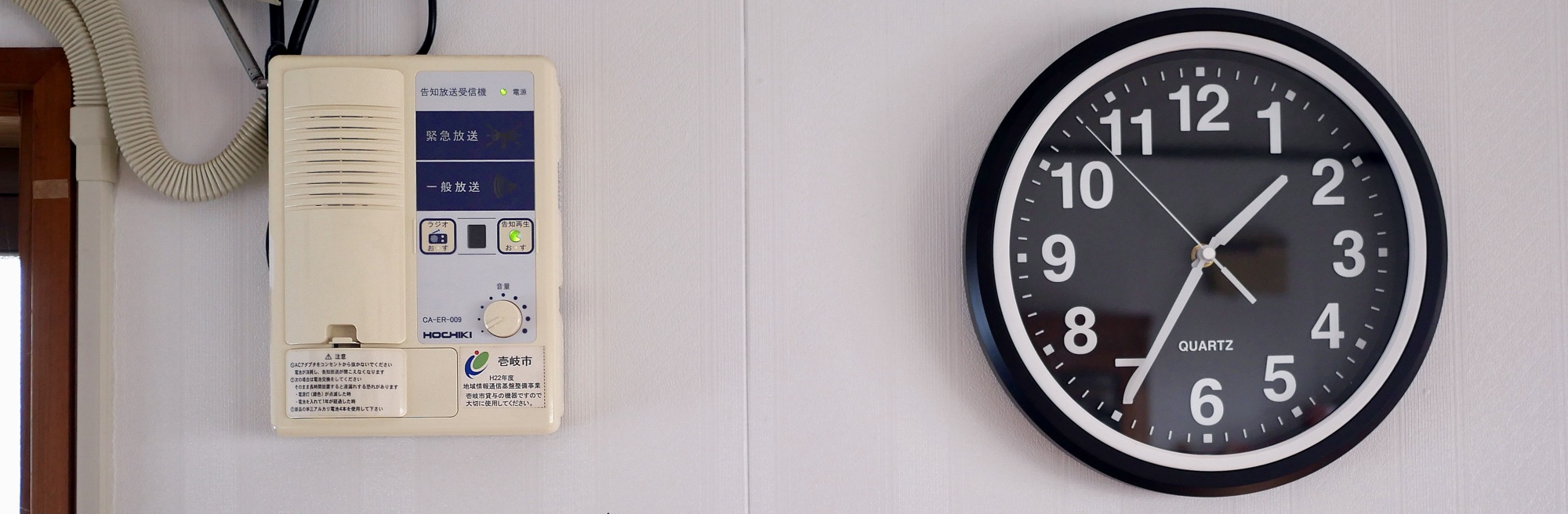 On a wall there is a home receiver on the left and a standard clock on the right
