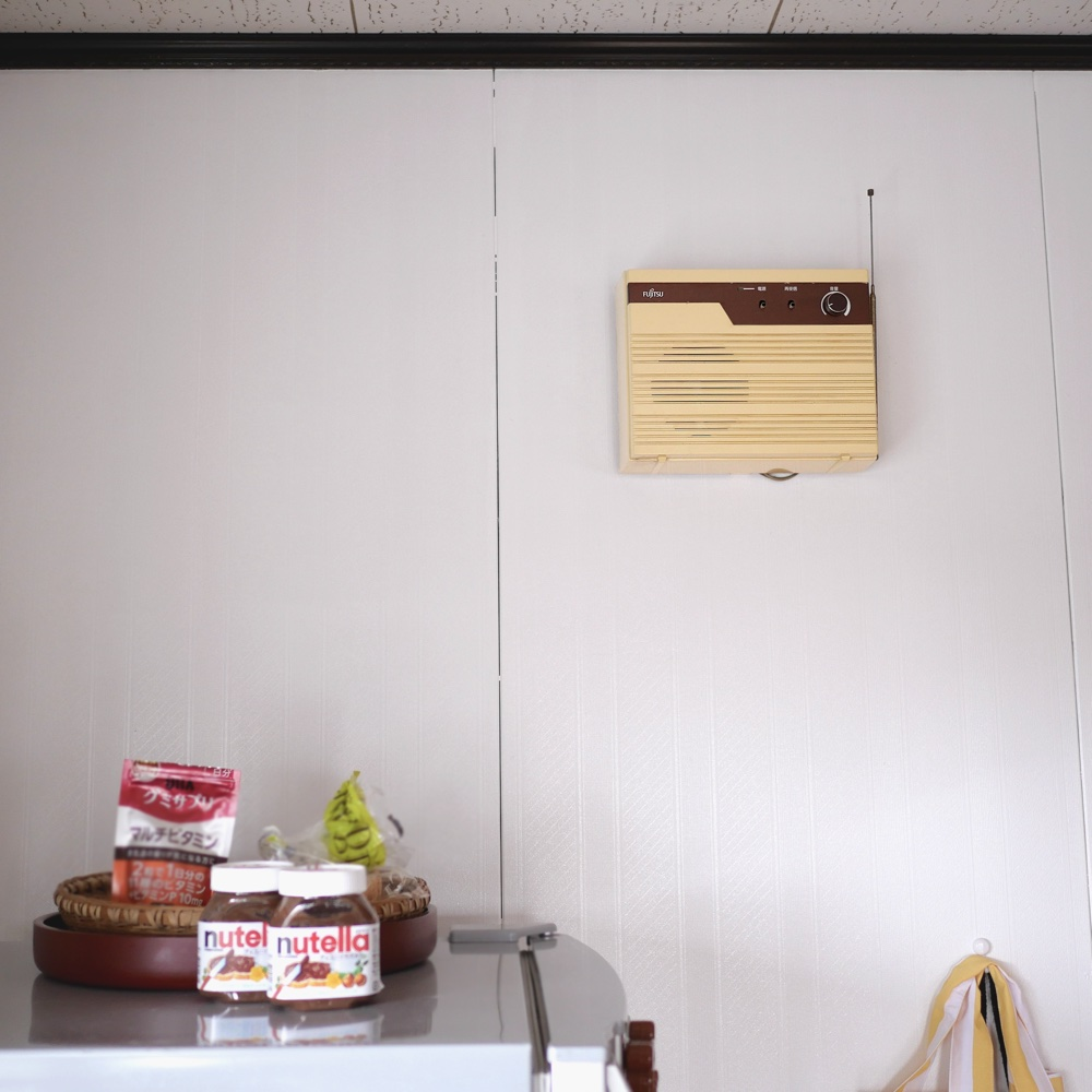 A radio-like object with metal antennae on the wall above a fridge with Nutella jars on it.