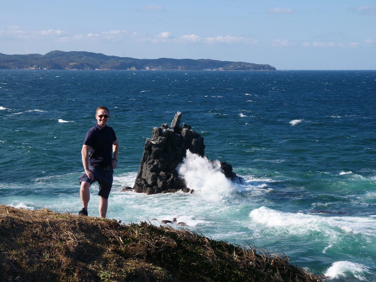Chad standing on a cliff, a massive wave crashes into a large rock formation in the ocean behind him