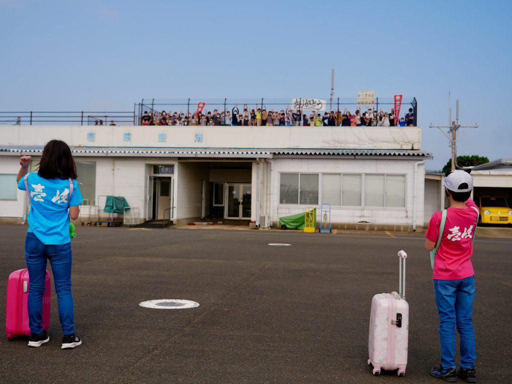"""two children wearing """"Iki"""" shirts wave to a crowd on top of a airport building"""