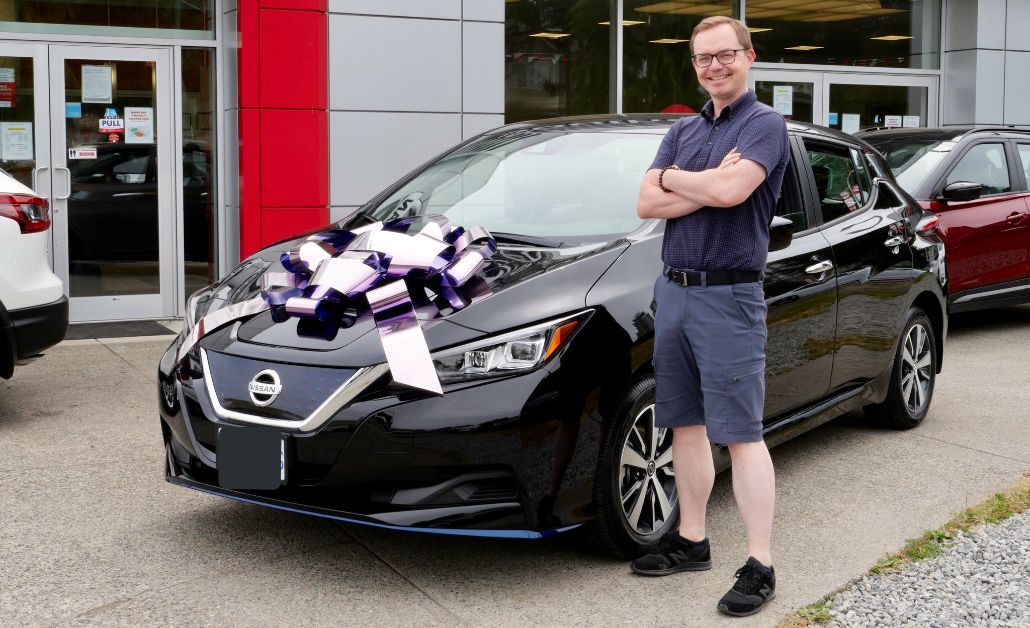 Chad standing in front of new car with a giant novelty bow on the hood