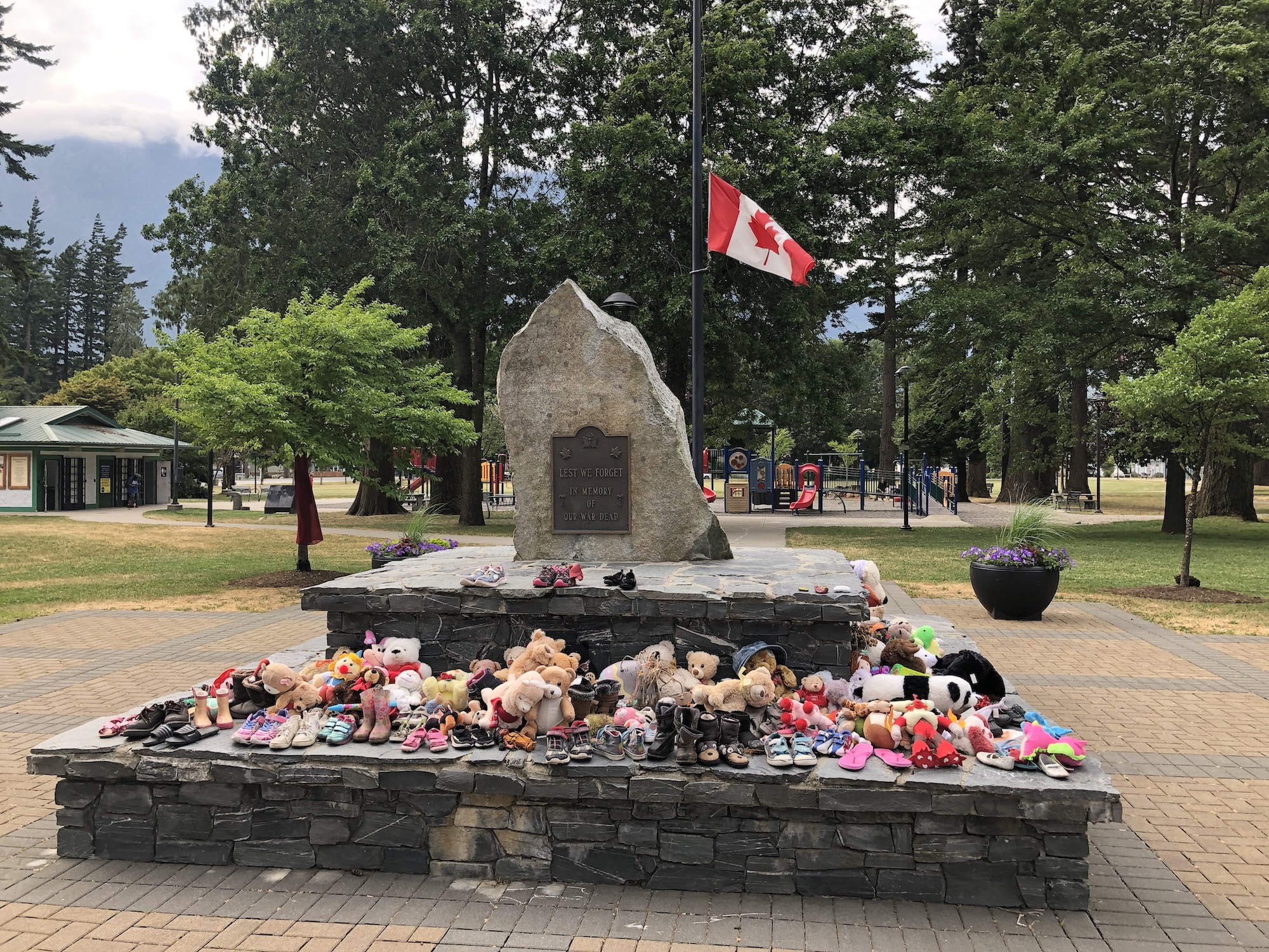 The cenotaph at Hope, BC. Flag is half-masted and shoes cover the cenotaph in memoriam of residential school victims.