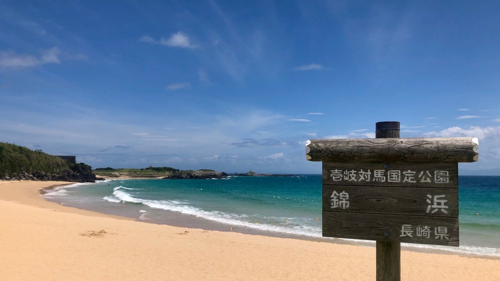 A sandy beach on a sunny day. A sign in the foreground indicating it is Nishiki-hama